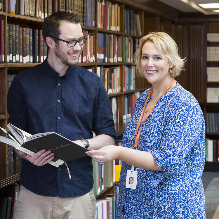 Librarian helping a young man in the Mitchell Library Reading room