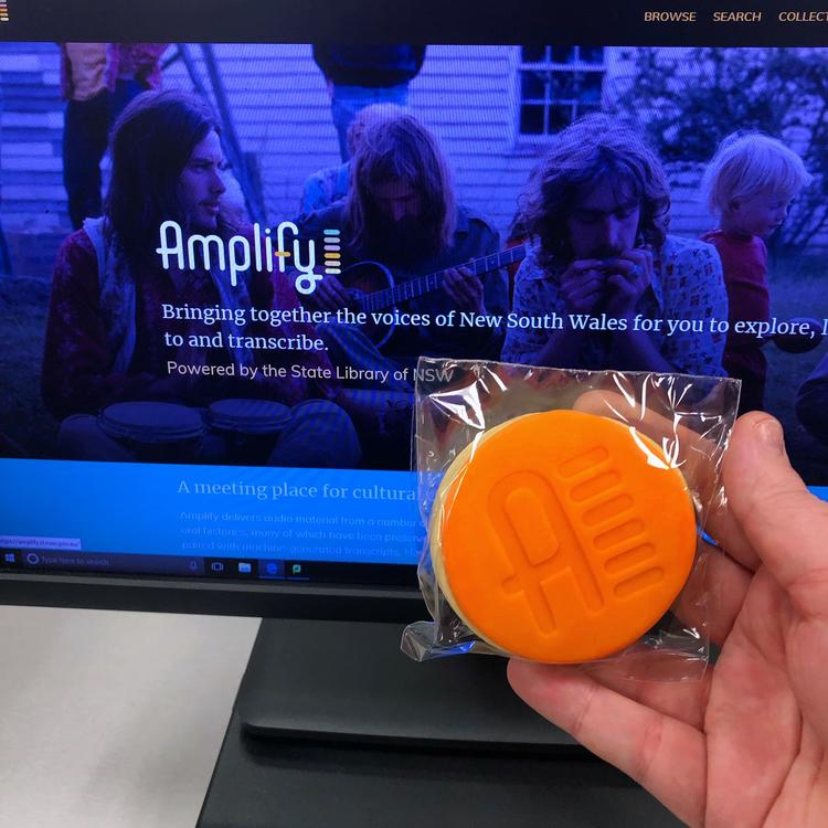 Word amplify on a screen with a hand holding an orange biscuit in front
