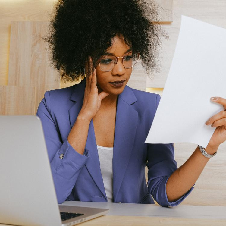 young woman at a desk looking at a piece of paper