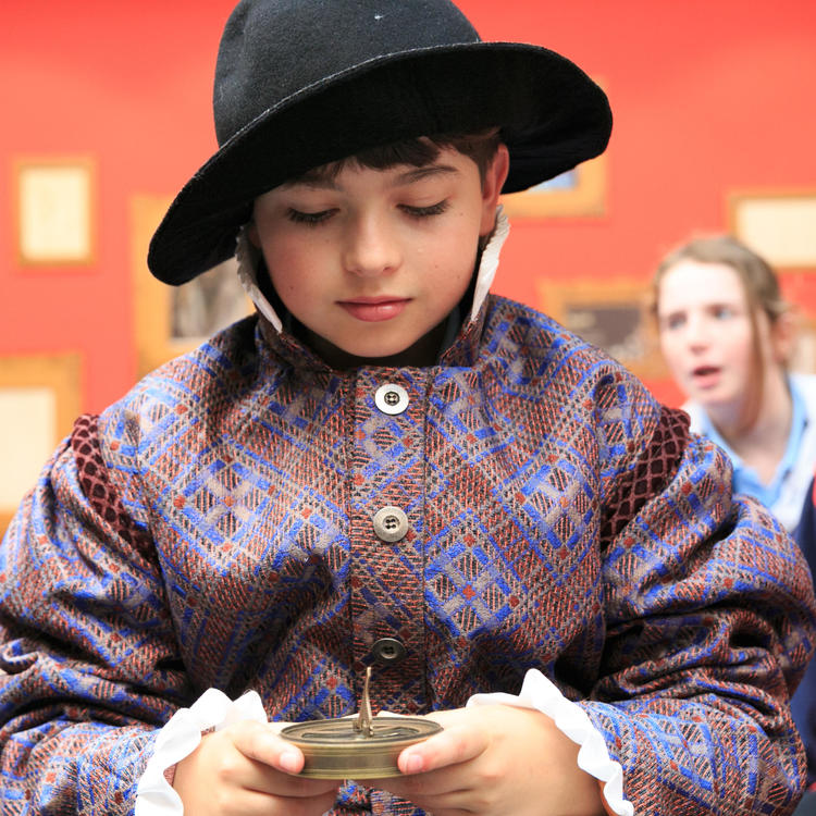 boy dressed in shakespearean costume looking down at a compass