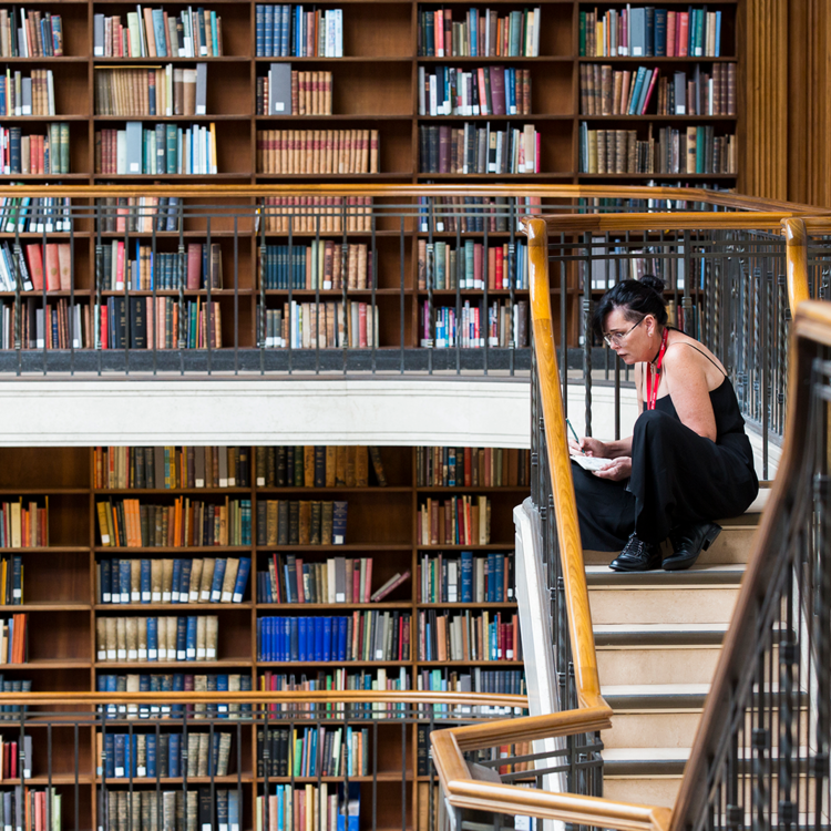Interior of library with shelves of books and woman sitting on stairs reading