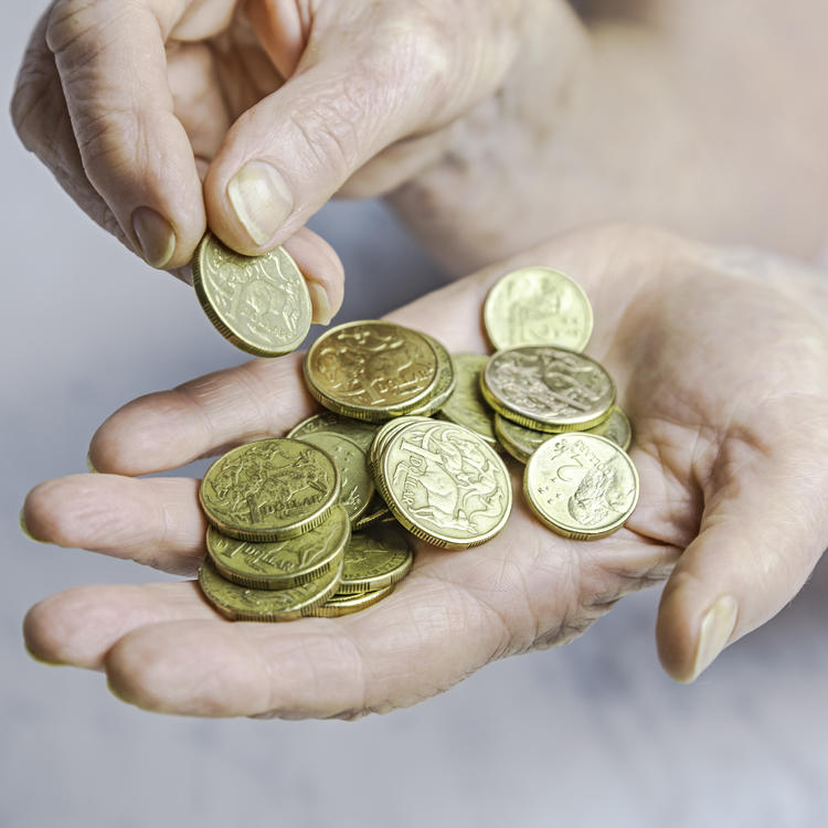 Hand holding a pile of one and two dollar coins