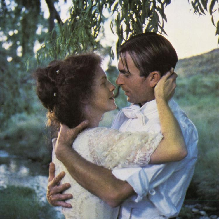 Still from film My Brilliant Career of man and woman standing and hugging next to a stream