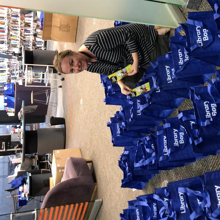 Woman on the floor packing blue library bags