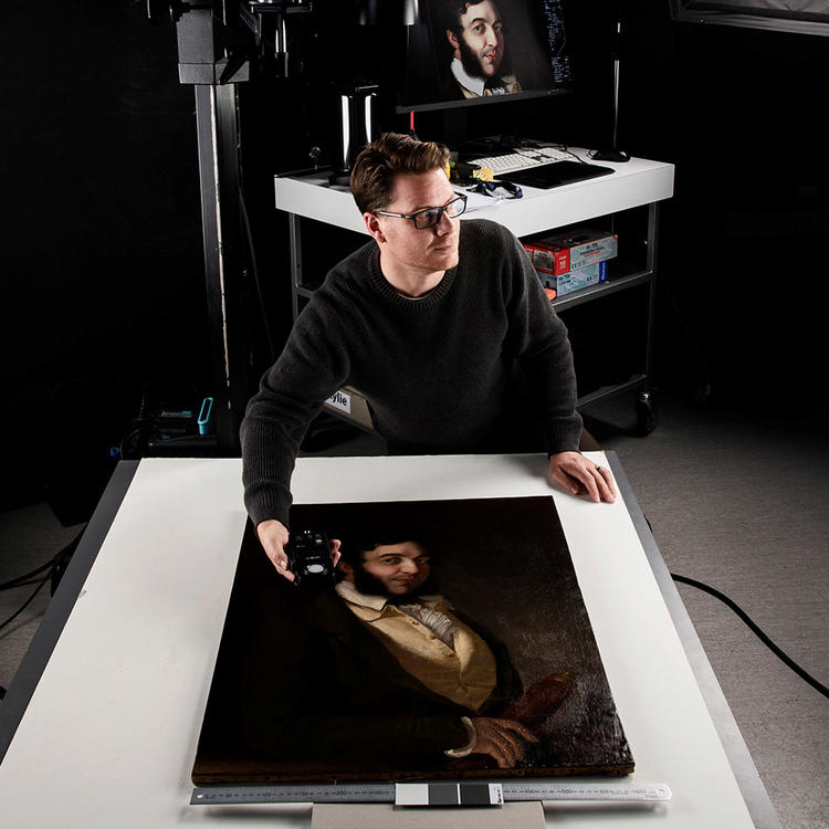 Between two large studio lights, a man leans over a painting on a desk, holding a light measurement device.
