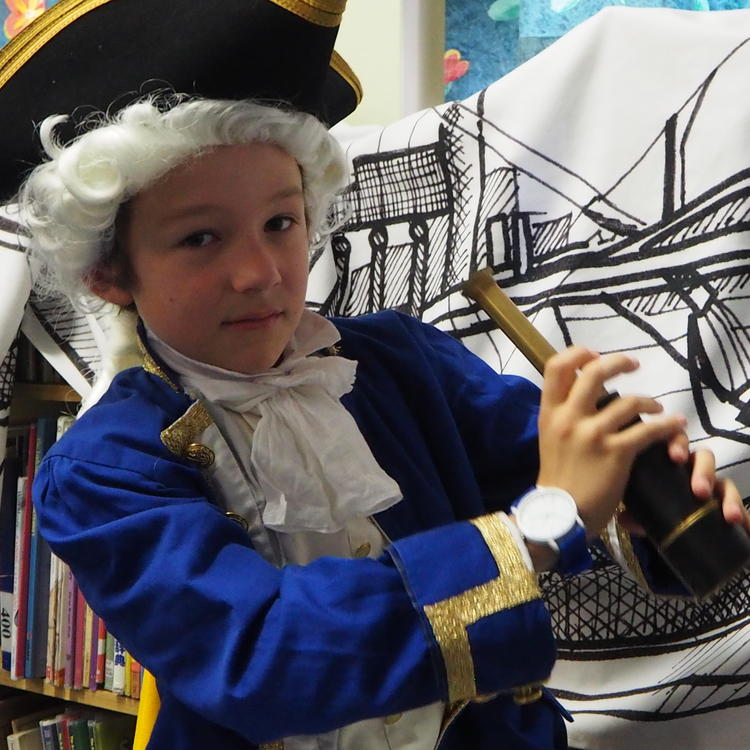 A student dressed as Captain James Cook holding a telescope