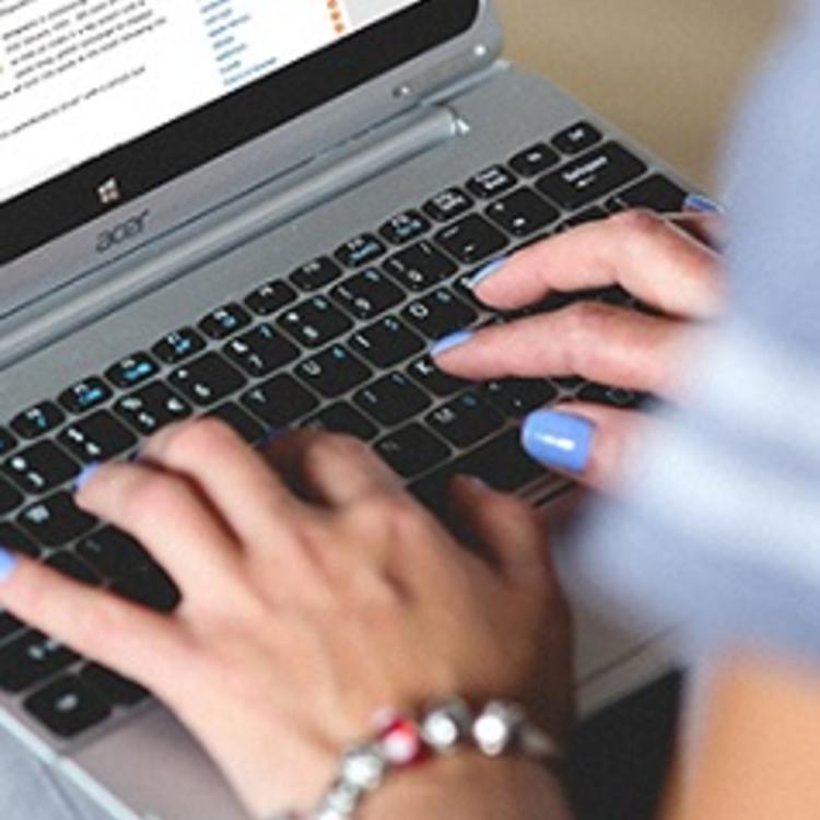 Woman using a laptop looking at the Public Library Services blog