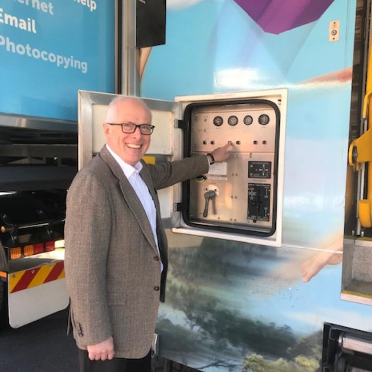 man at control panel of mobile library vehicle