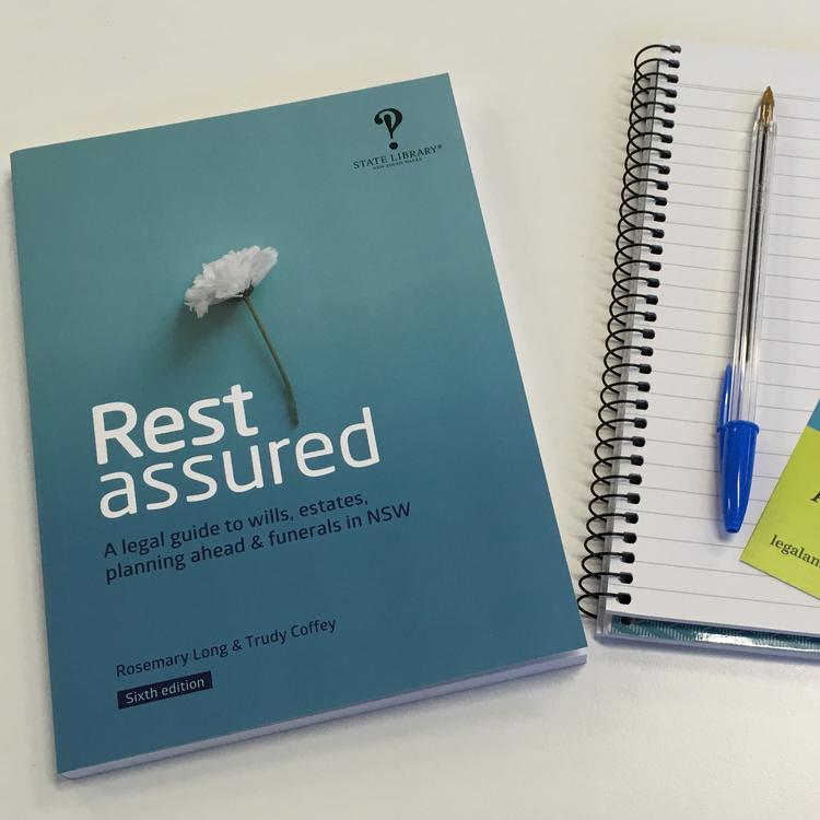 A blue book called Rest assured on a table next to a notepad and pen