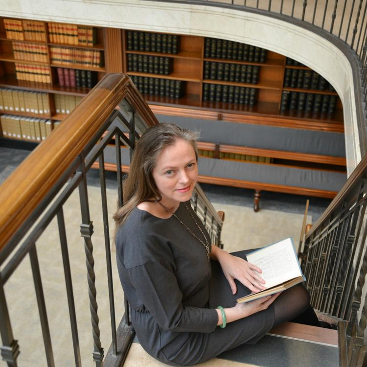 Rachel Franks sitting on a staircase with an open book in her lap