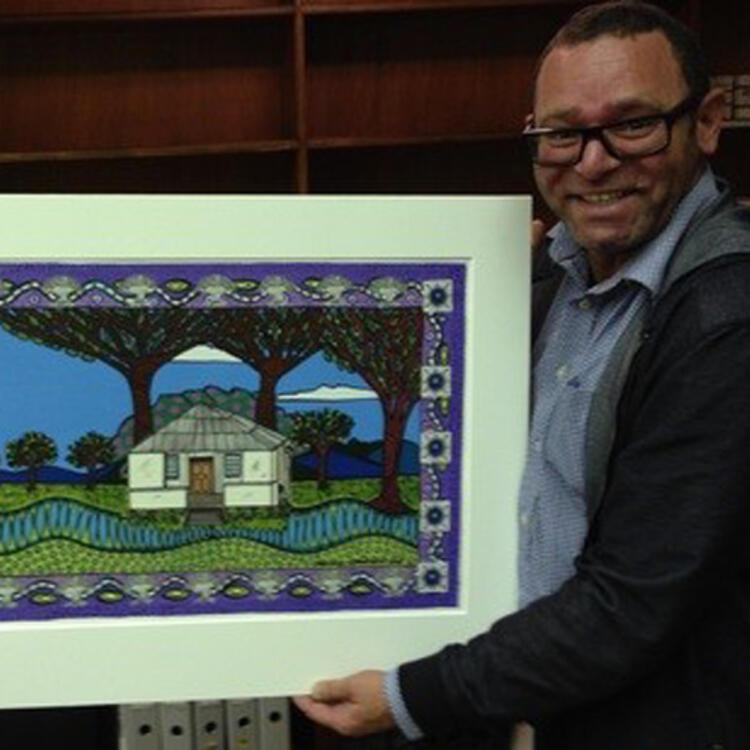 A man holding up an original artwork by Bronwyn Bancroft