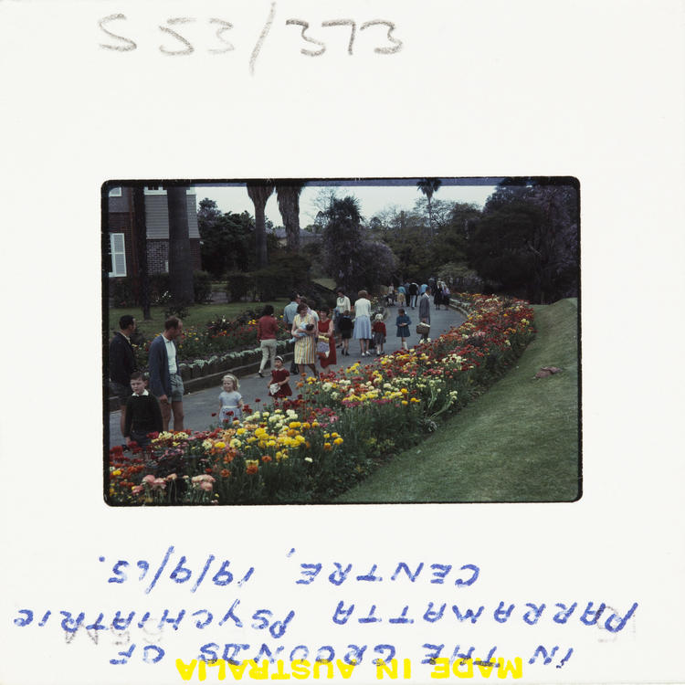 A 60s Kodak colour slide showing people walking down a path with flower beds on either side.