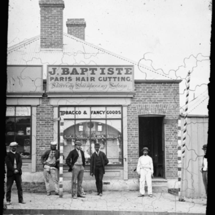 Black and white photo of people standing out the front of an 1800s hairdressing salon