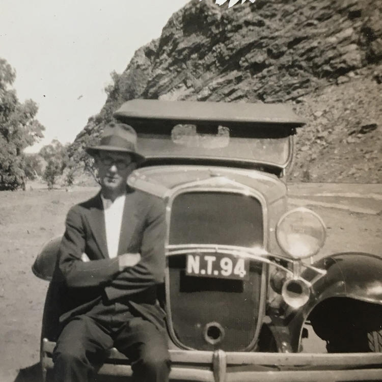 Francis McGarry sitting on front of car, 1939