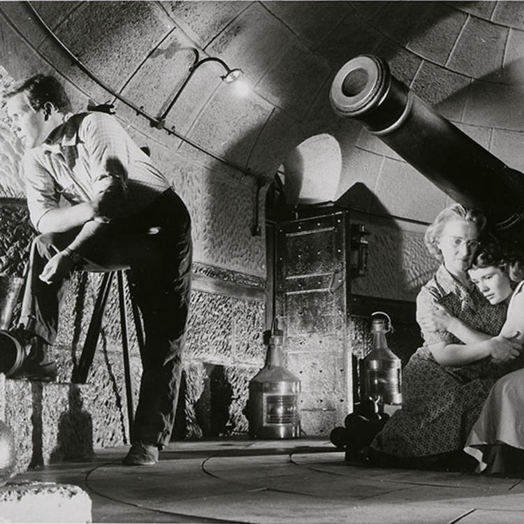 two woman sitting under a cannon, holding each other in a tower while a man stands, staring out of the tower window