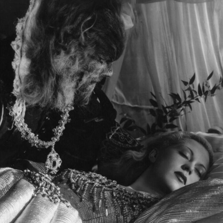 black and white image of a beast leaning over a sleeping woman