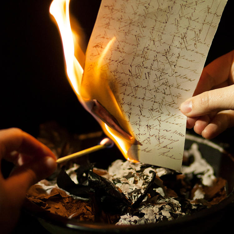 Hands holding a lit match to a burning piece of paper.