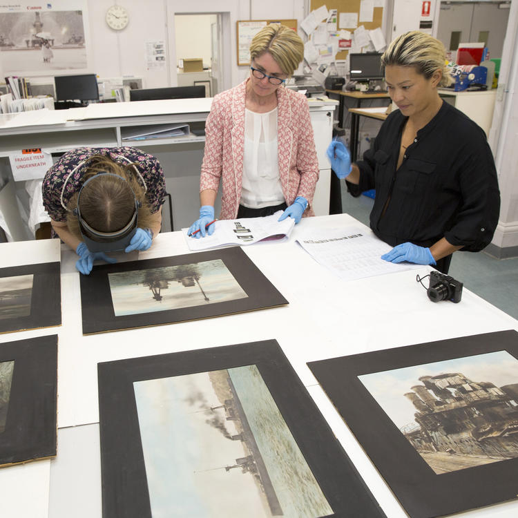Three women stand at a table covered in photographs. One woman leans over a photograph to examine it with a set of magnification goggles.