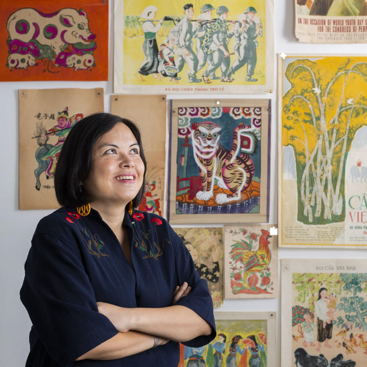 A woman stands in front of a wall of Vietnamese art posters, smiling.
