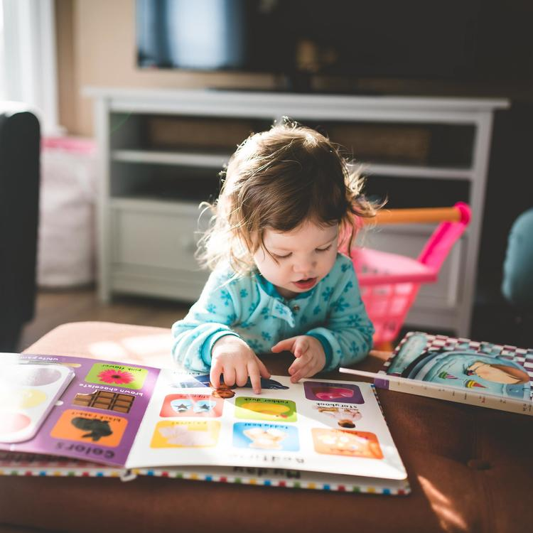 Child reading a book at a coffee table