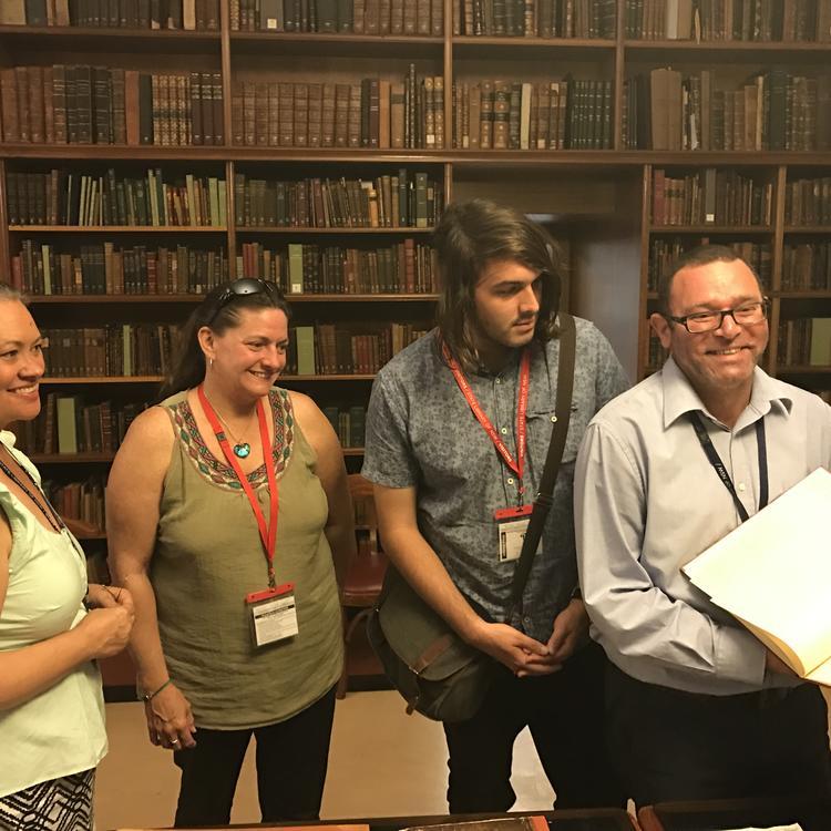 4 people looking at a manuscript