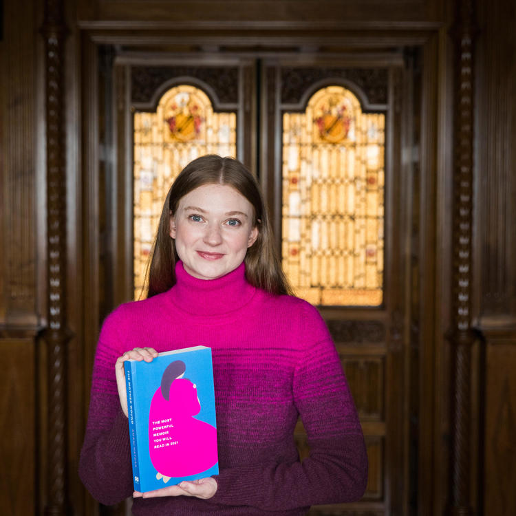 Bri Lee holding a copy of the book The Mother Wound