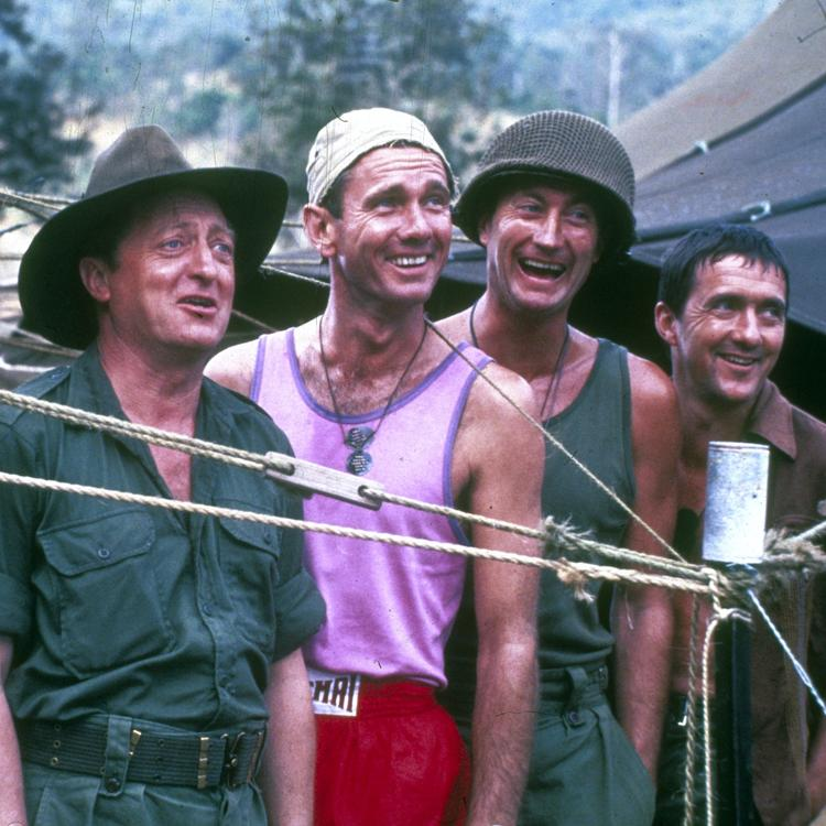 4 men standing behind a fence smiling and laughing
