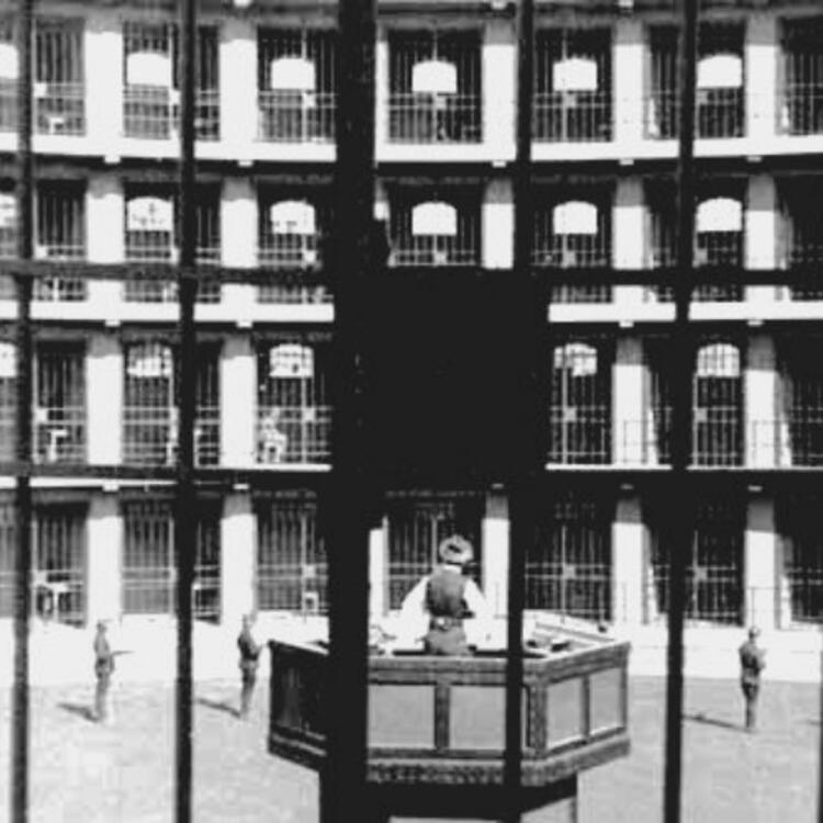 black and white image of prison cells from behind bars, guards patrol the courtyard the cells face towards