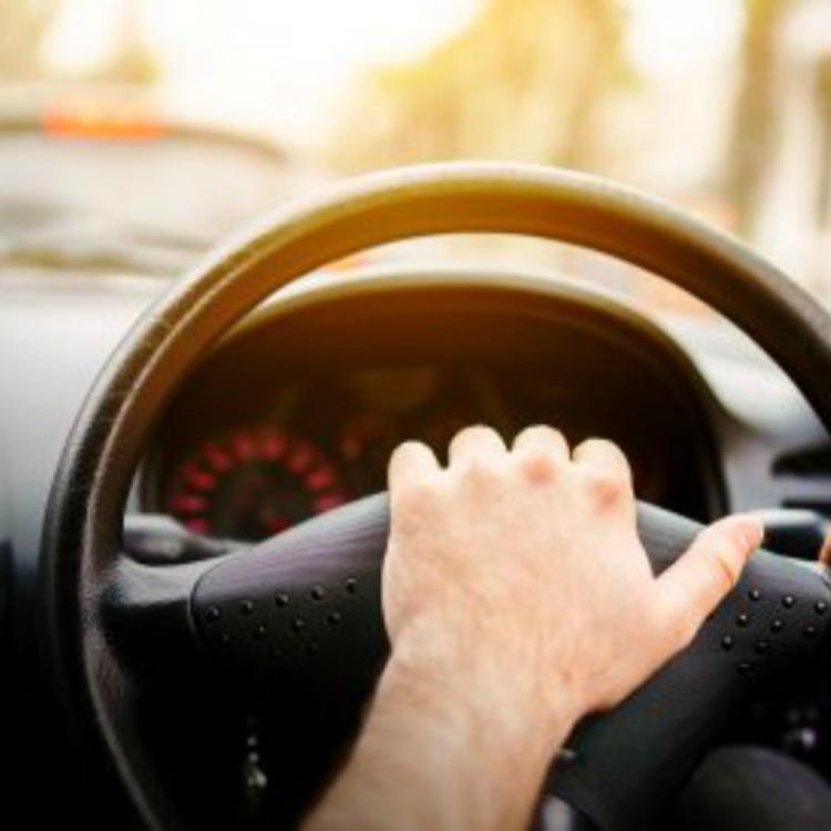 Image of the interior of a car dashboard with hands on the steering wheel