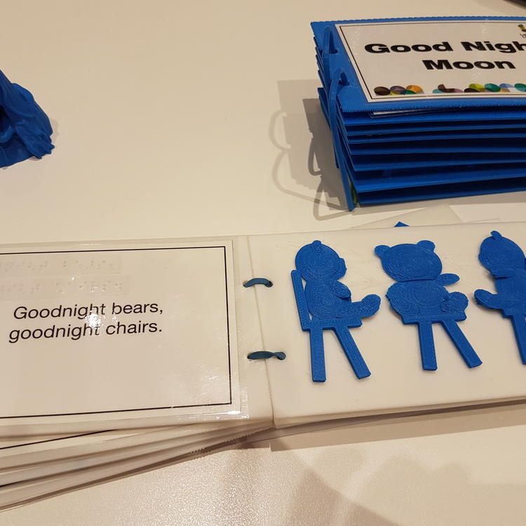 shows a page of a 3D printed book with three bears sitting on chairs