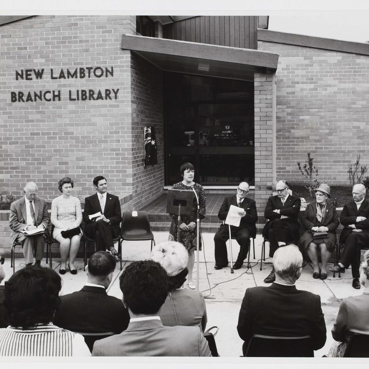 Black and white photograph of woman giving a speech in front of a new library building