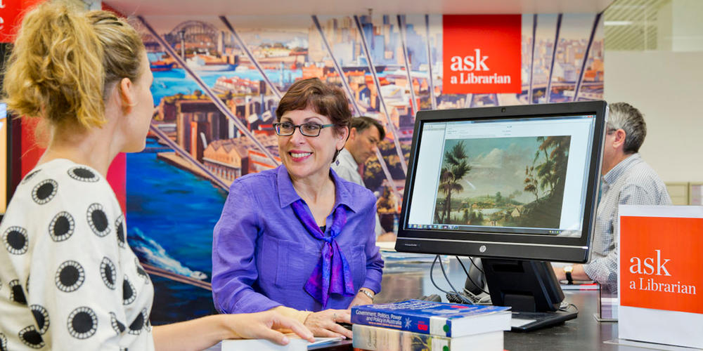 Staff helping client with research at the Ask a Librarian desk