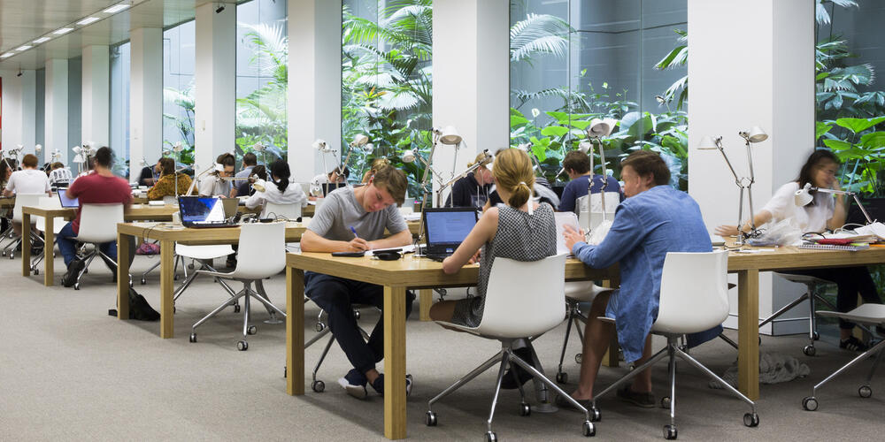 Students sitting at communal tables by the atrium in the reading room