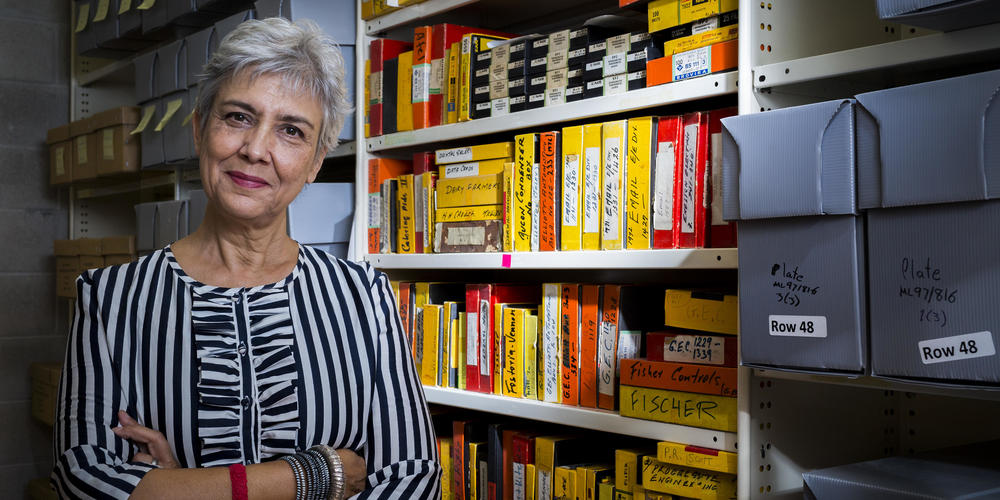 State Library Reader in Residence, Caroline Baum standing in Library stacks