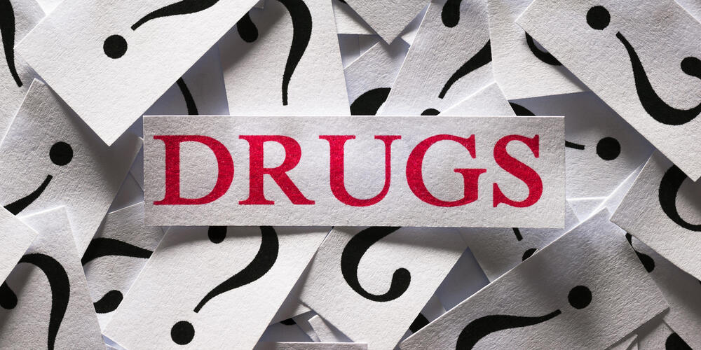 The word drugs on top of question marks