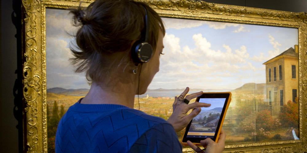 Woman with headphones looking at iphone in front of large painting