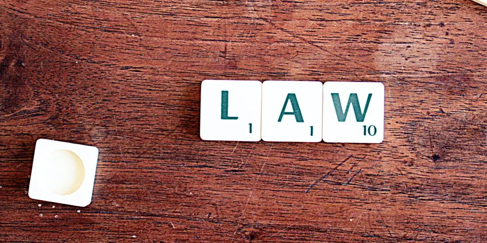 The word law spelled out in scrabble tiles on a brown timber table