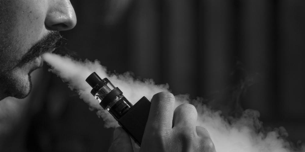 Black and white photograph of man blowing vapour out of a vape pen