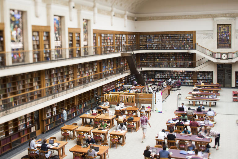 Mitchell Library Reading Room with booklined shelves and tables and desks