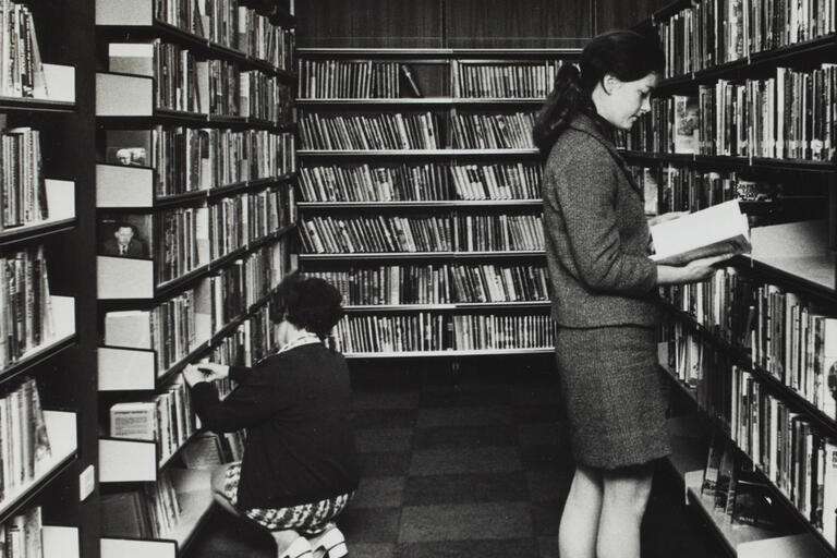 BW photo of two women in library looking through books on shelves