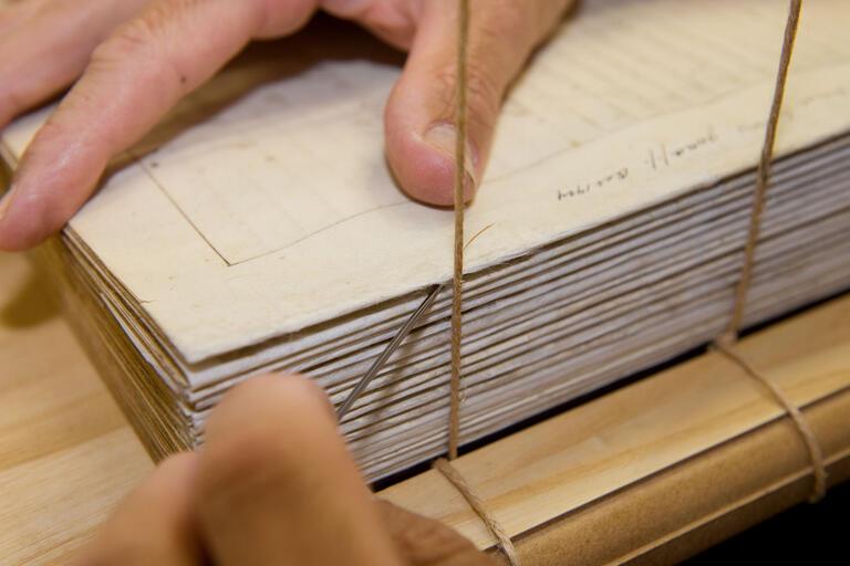 Conservator binding a book