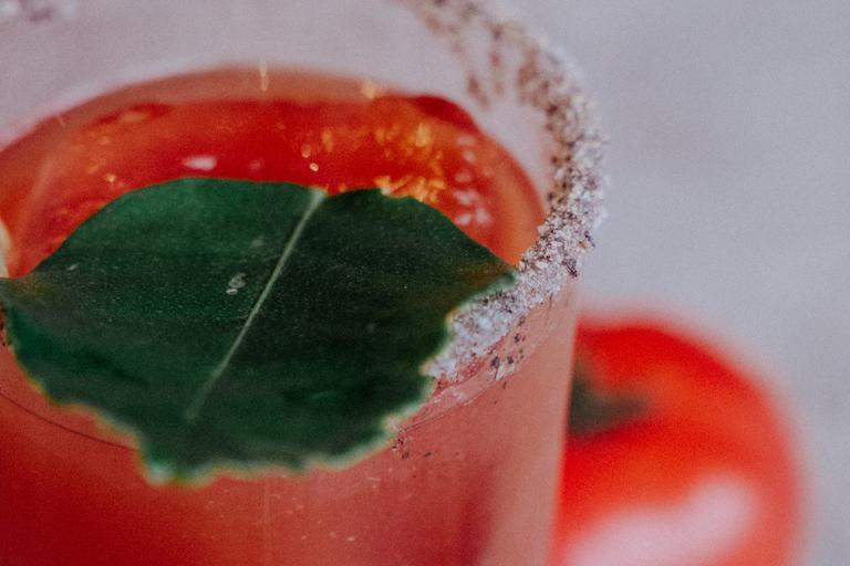 A red drink in a glass with a salted rim