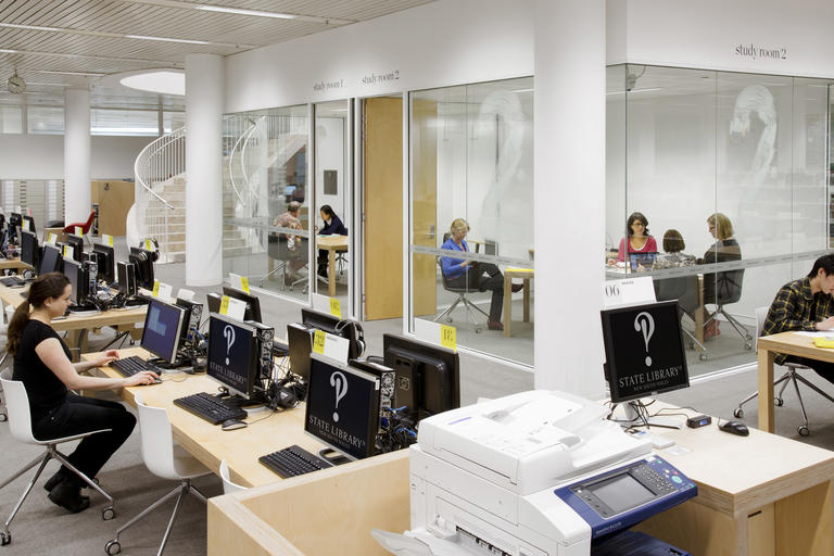 People working inside glass walled study rooms