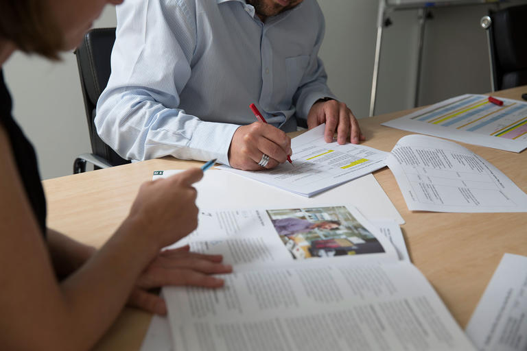 Man and woman working on documents at desk