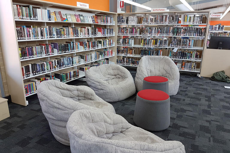 Three bean bag style chairs next to the Teen Fiction and Sci-Fi & Fantasy shelves in a library.