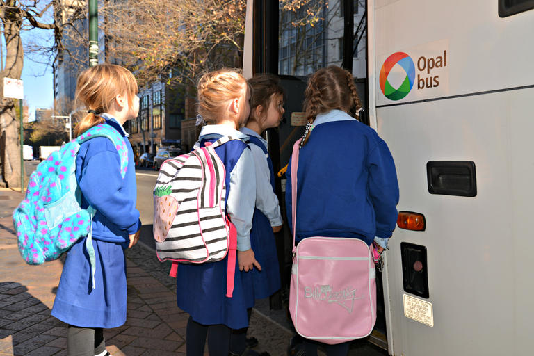 four five year old girls boarding a bus