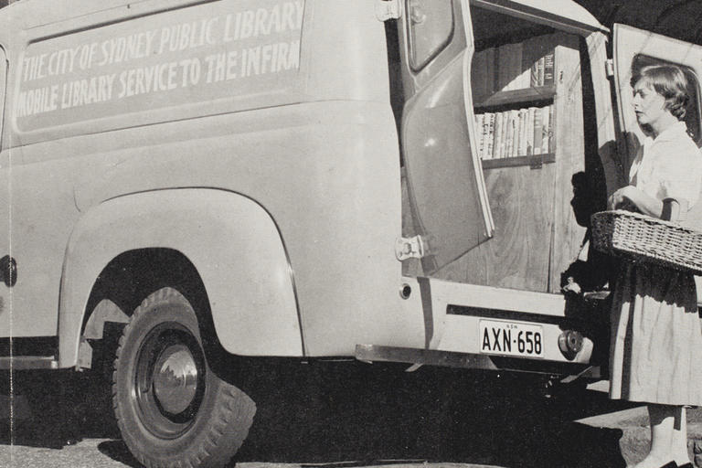 Woman with basket of books next to van b/w photo