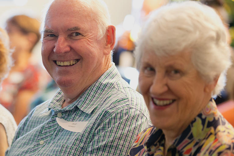 Two smiling older people in audience