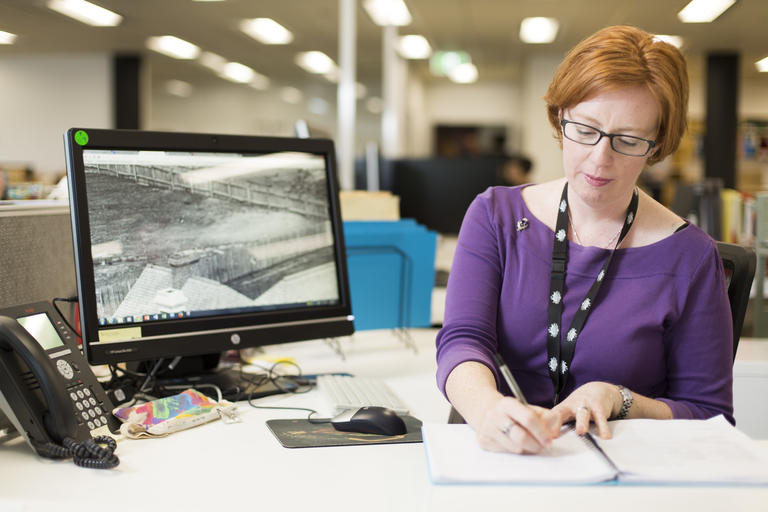 Woman at desk writing in notepad