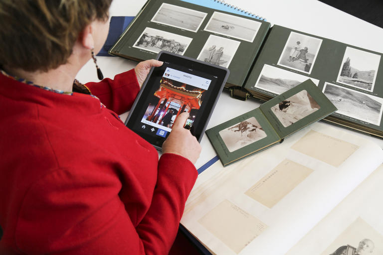 Woman using tablet to capture image from photo album